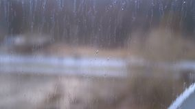Rain outside the window. Raindrops flow down the glass. Bad, depressive weather. Autumn or spring stock video footage