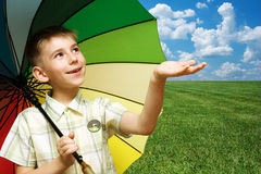 The rain is over. A smiling boy with a colorful umbrella in his hand is glad that the rain is over Royalty Free Stock Image