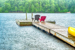 Rain over the wharf. Heavy rain over a deck with two chairs and a kayak Stock Photo
