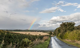 After the Rain. Partial rainbow and wet country lane after a storm in Scotland Royalty Free Stock Photo