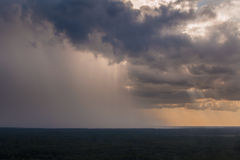 Rain pouring down from clouds at a distance Stock Photo