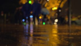 Rain pouring in night city. It is raining in the city at night. Autumn scene with raindrops falling in puddles, cars passing by and people with umbrellas walking stock video