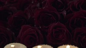 Rain pours candle on background of red roses sorrow for the dead slow motion stock footage video. Rain pours candle on a background of red roses sorrow for the stock video footage