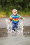 Rain puddles. Boy jumping and splashing in rain puddle Royalty Free Stock Photography