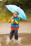 Rain puddles. Boy splashing in puddle smiling holding a blue umbrella Royalty Free Stock Image