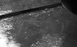 RAIN PUDDLES WITH RAINDROPS. BLACK AND WHITE PHOTO OF RAIN PUDDLES WITH RAINDROPS Stock Images
