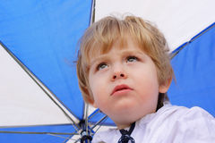 Rain rain go away. Closeup of a boy looking toward the sky holding an umbrella stock photography