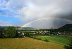 Rain and rainbow. Alpine sunny field in valley in Switzerland Royalty Free Stock Image