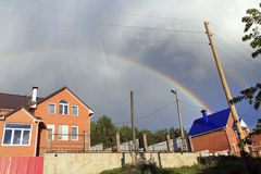 After rain. Rainbow after rain above the bright red houses Royalty Free Stock Photos