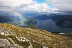 Rain with rainbow on the fjords Stock Image
