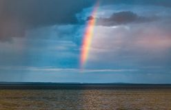 Rain and rainbow over the water stock images