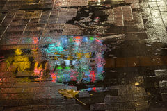 After the rain. Reflexion on the sidewalk of the neon lights at the sidewalk after the rain royalty free stock images