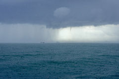 Rain in sea with dark clouds and tornado. Small boat and tornado in the raining sea in Krabi, Thailand Stock Image