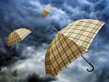 Rain season. Umbrellas in a dark and stormy autumn sky Stock Photos