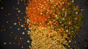 A rain from seeds drops on three bunches of lentils and mung in slow motion. stock footage