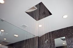 Rain Shower. Shower head pous like rain in a stone and glass shower Royalty Free Stock Photography
