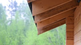 Rain flows down from the roof of a wooden house large drops in cloudy rainy weather