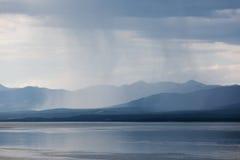 Rain shower over Marsh Lake Yukon Territory Canda. Heavy rain shower over Marsh Lake Yukon Territory Canada and distant mountain range Stock Image