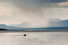 Rain shower over Marsh Lake Yukon Territory Canda. Heavy rain shower over Marsh Lake Yukon Territory Canada and distant mountain range with a small motorboat out Stock Photos