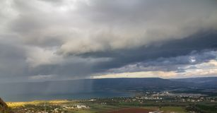 Rain Showers over the Sea of Galilee, Israel`s natural water sources, on a winter day with dramatic dark rain clouds scenery,. Southern basin of lake Kinneret stock image
