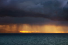 Rain showers on the sea at sunset Royalty Free Stock Photos