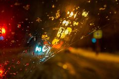 Rain with snow on the windshield, the lights of the big city through the water, wallpaper. Rainy evening, blur. highway road in the snow, cityscape, background stock images