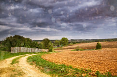 Rain. Spring storm clouds above country road. Rain and spring storm clouds above country road. Village and arable land field in spring Royalty Free Stock Image