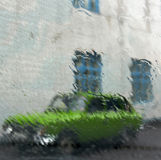 Rain steams on the window. Pattern of water steams on window glass during the rain with green car and building wall with blue windows outside Stock Image