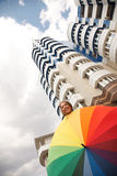 Rain stoped. Cheerful woman is standing near modern  building with colorful umbrella .Low Angle View Royalty Free Stock Photos