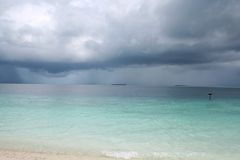 Rain storm above tropical sea. A tropical rain storm approaching a sandy beach, on Filitheo Island, Maldives Royalty Free Stock Photos
