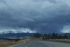 Rain / Storm clouds on the road to Banff. With snow capped Canadian Rockies on the horizon royalty free stock image