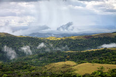 Rain stripes in the sky showering hills covered with woods Royalty Free Stock Photography