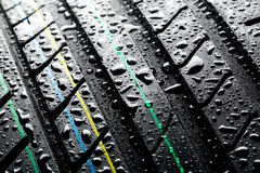 Rain on summer car tire. A closeup image of a wet summer car tire with rain drops on it Stock Photo
