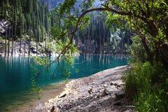 Rain in sunlight on a mountain lake Stock Image