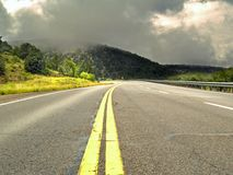 Rain and sunshine. On a road uphill Stock Photography