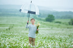 Rain and sunshine with a smiling boy holding an umbrella and running through a meadow of wildflowers dundelions chamomile daisy an Royalty Free Stock Photo