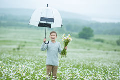 Rain and sunshine with a smiling boy holding an umbrella and running through a meadow of wildflowers dundelions chamomile daisy an Stock Images