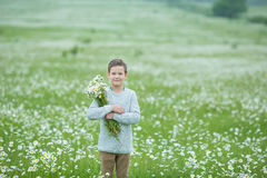 Rain and sunshine with a smiling boy holding an umbrella and running through a meadow of wildflowers dundelions chamomile daisy an Royalty Free Stock Photos