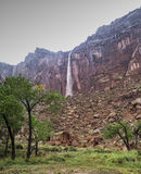 Through the Rain to the Waterfall. Waterfalls coming off the top of a red rock cliff in Capital Reef National Park Utah USA. A once in a lifetime picture from Stock Photography
