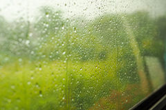 Rain on the train window. Blurred image of corn fields from a windows glass with water drop on a rainy day Stock Photography