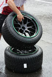 Rain tyres. Mechanic takes a wheel mounted with wet tyre while rain is falling Stock Photography