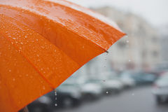 Rain on umbrella. Rain drops falling from a bright orange umbrella royalty free stock images