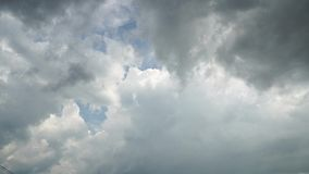 Rain is visible between thunderclouds. Storm clouds and light in sky. 4K video
