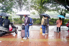 The rain waiting on bus home people. Spring Festival approaching, the bus in the rain waiting for the bus, people go home in Shenzhen, China stock photo