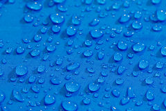 Rain Water droplets on blue fiber Royalty Free Stock Images