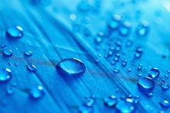 Rain water droplets. On  blue waterproof fabric Stock Photography