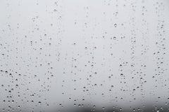 Rain water droplets on glass window with gloomy sky Stock Photography