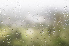 Rain water droplets on glass window with scenic greenery view Royalty Free Stock Photo