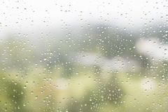 Rain water droplets on glass window with scenic greenery view Stock Photo