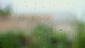 Rain and water drops falling on glass during rain storm, close up. stock video footage